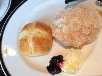 お皿に乗ったアフタヌーンティーのお菓子の写真。スコーンとオレンジブリオッシュに、ジャムとクロテッドクリームが添えられている