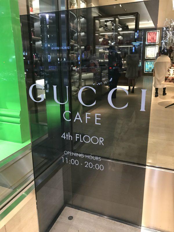 Gucciブティックの入り口の横にカフェの看板があります。