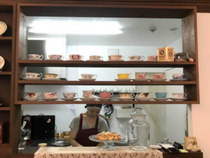 カウンターには可愛いティーカップが並んでいます。奥にいるのはオーナーの真弓さん。