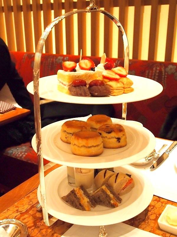 ケーキスタンドに盛り付けられたアフタヌーンティーのティーフード。3段スタンドの場合、スコーンは2段目に盛り付けられるのが基本です。