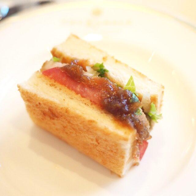 じっくり火を入れたイベリコ豚のローストにオニオンキャラメリゼのコンディマンとフレッシュトマトを挟んだトーストサンドウィッチ