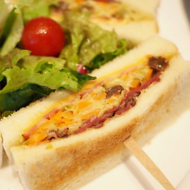 マンハッタンサンドウィッチ具材はパストラミビーフ、カレー風味のコールスロー、チェダーチーズ、ベーコン